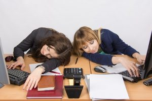 Two young women asleep on computer desks